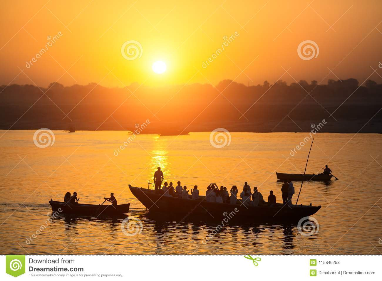 Silhouettes of boats with pilgrims during sunset on holy Ganges river, Varanasi .