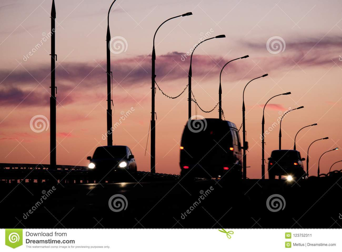 a840eb3672 Silhouettes of cars and vans in front of pink-orange sunset sky with  silhouettes of streetlamps