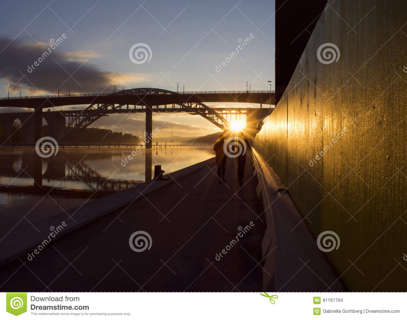 Silhouettes of couple running at beautiful, early dawn under a bridge.