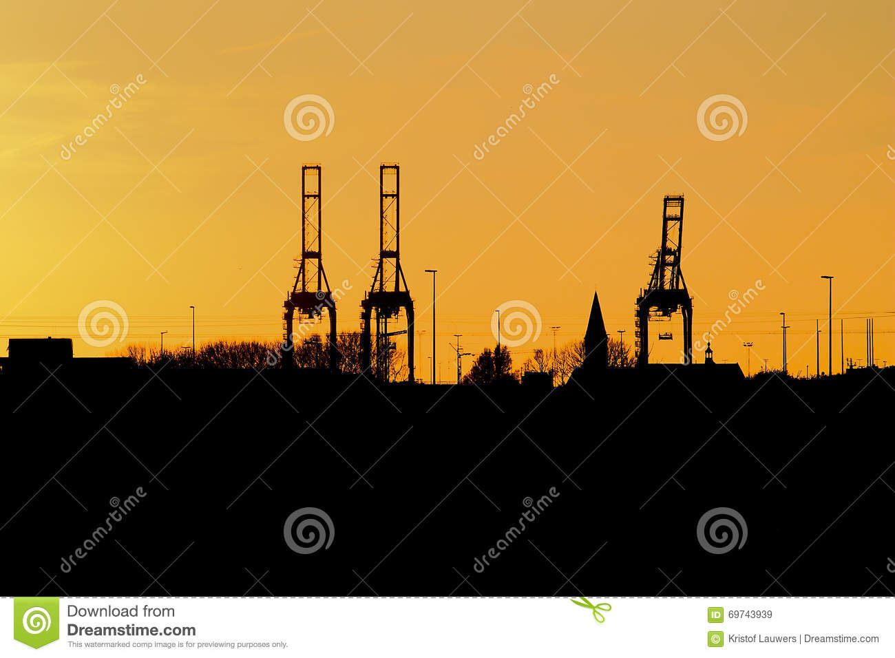 Silhouettes of cranes and church in evening light