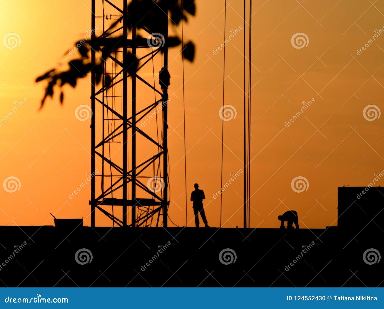 Silhouettes d une grue et des travailleurs de la construction sur un fond de coucher du soleil