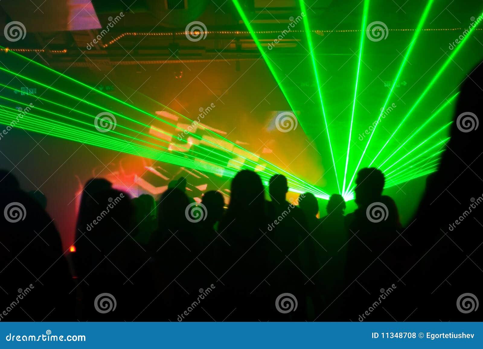 Silhouettes des gens de danse dans la lumière laser verte