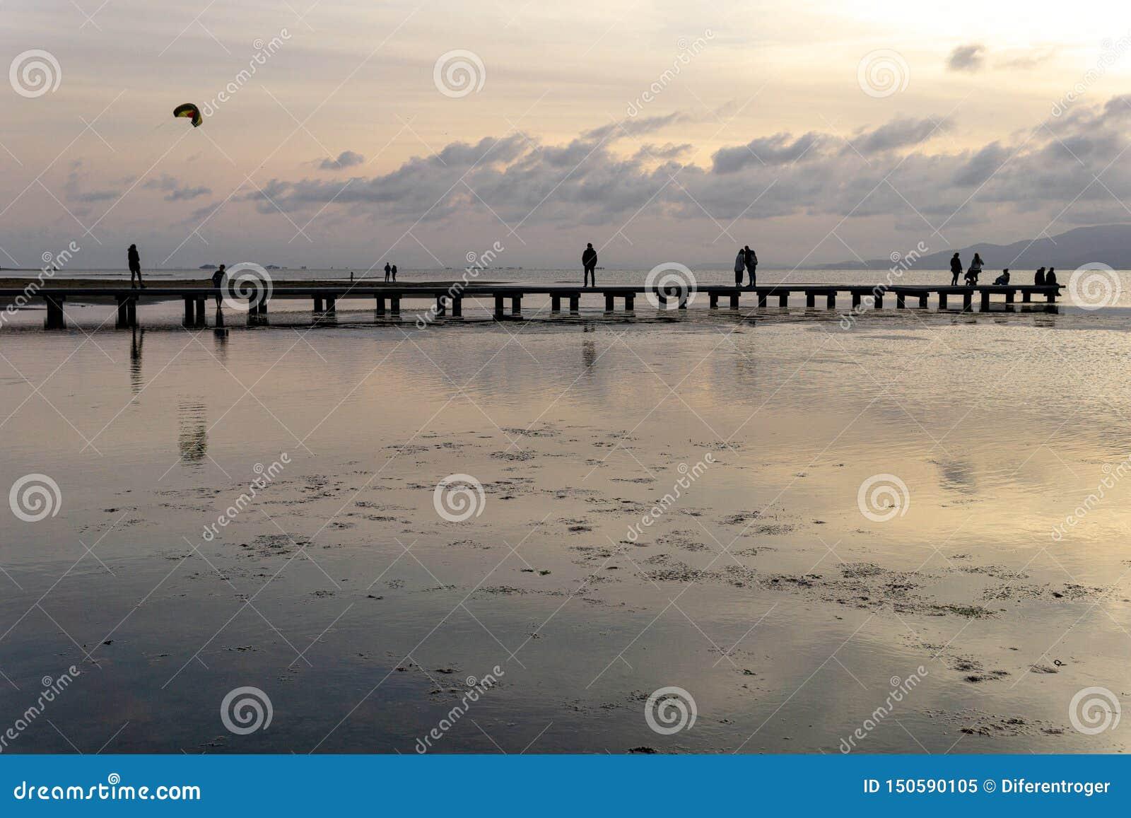 Silhouettes des personnes méconnaissables sur un pilier au coucher du soleil