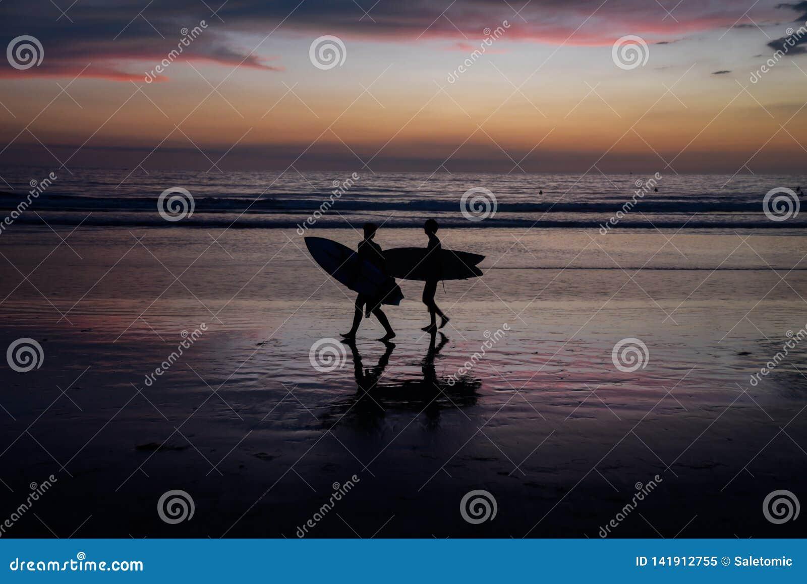 Silhouettes des surfers au coucher du soleil