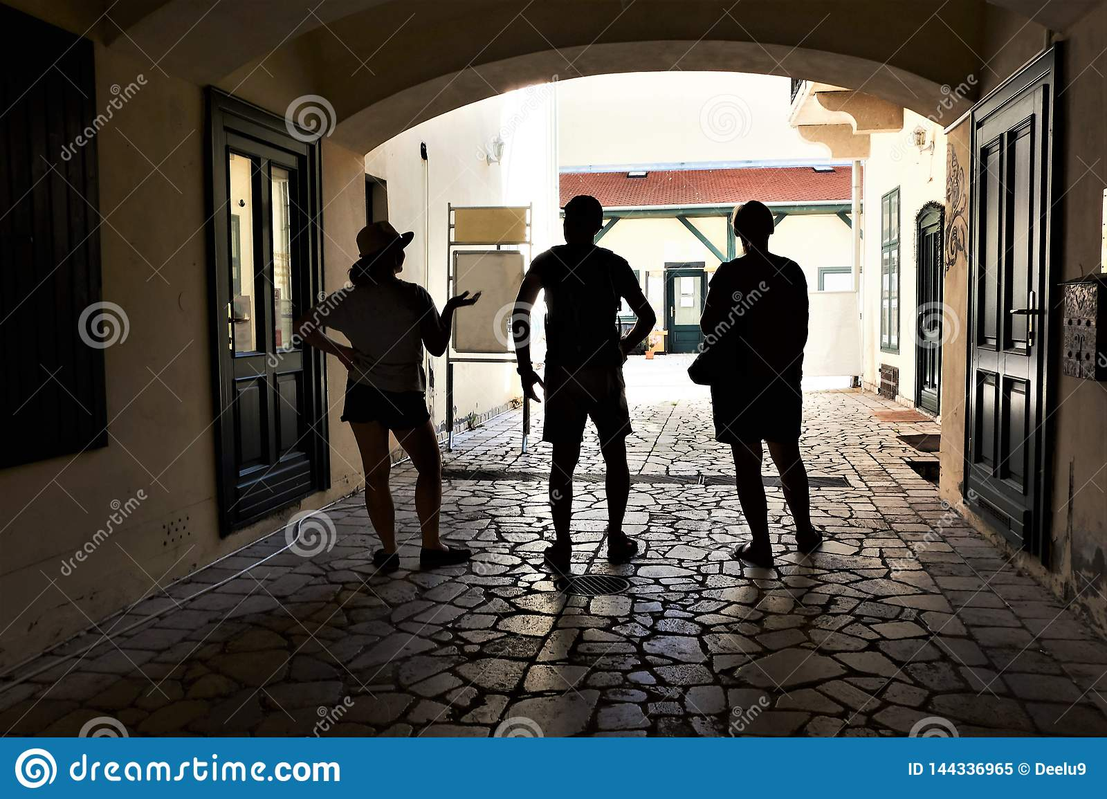 A family of three travelers seeking shade in an alleyway in a historic town of Eger, Hungary