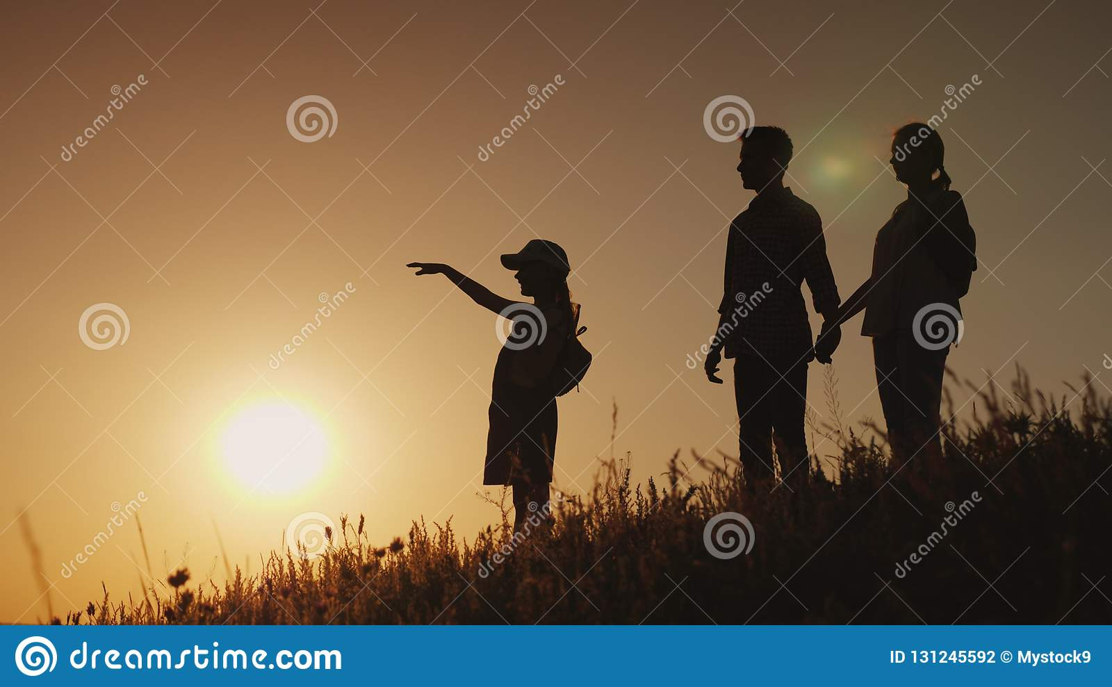 Silhouettes of a happy family, together they meet the dawn in a picturesque place
