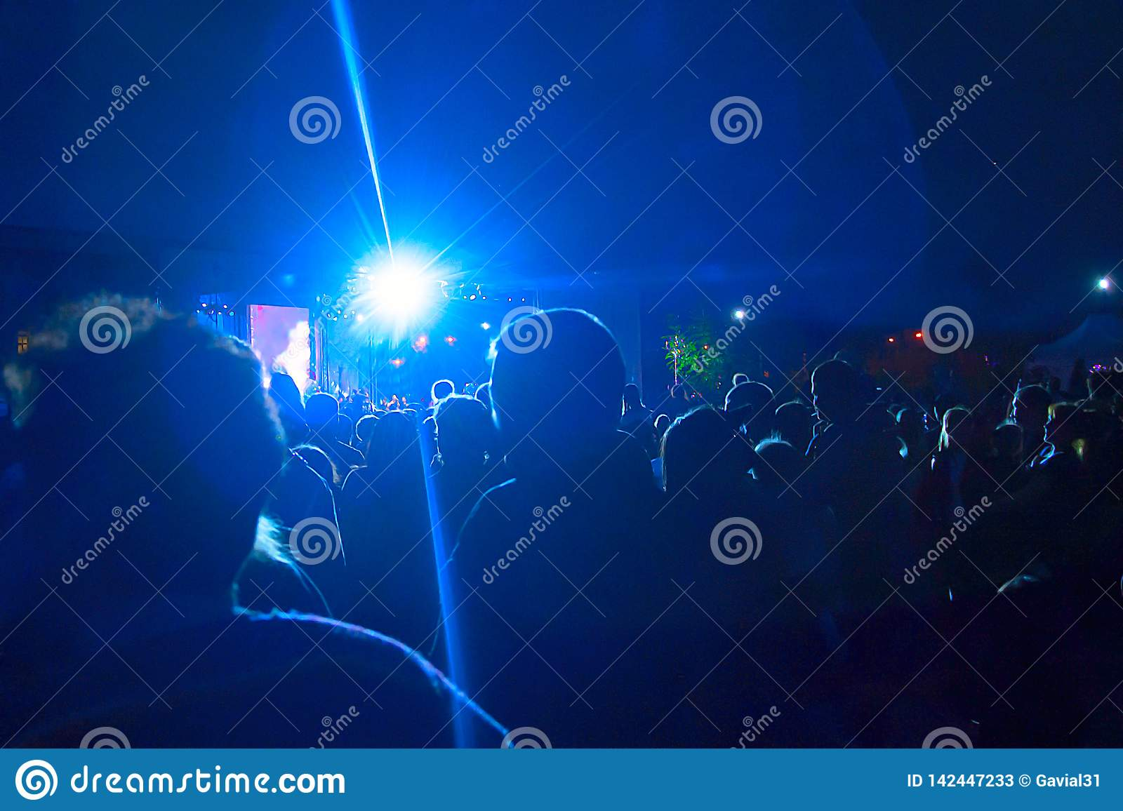 Silhouettes of a large number of people on the background of spotlights. Concept: celebration, rally