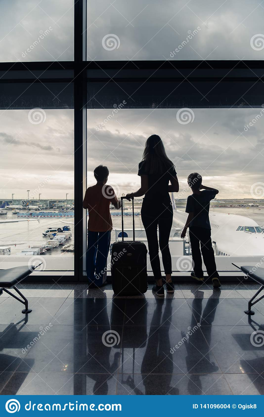 Silhouettes of mom with kids in terminal waiting for flight