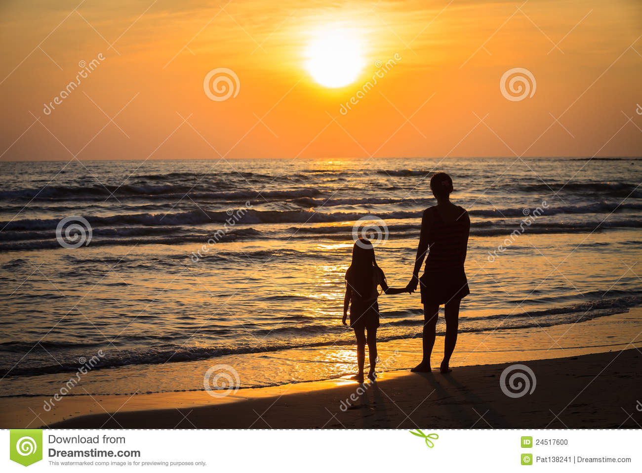 Mother And Daughter Walking On Beach At Sunset High-Res