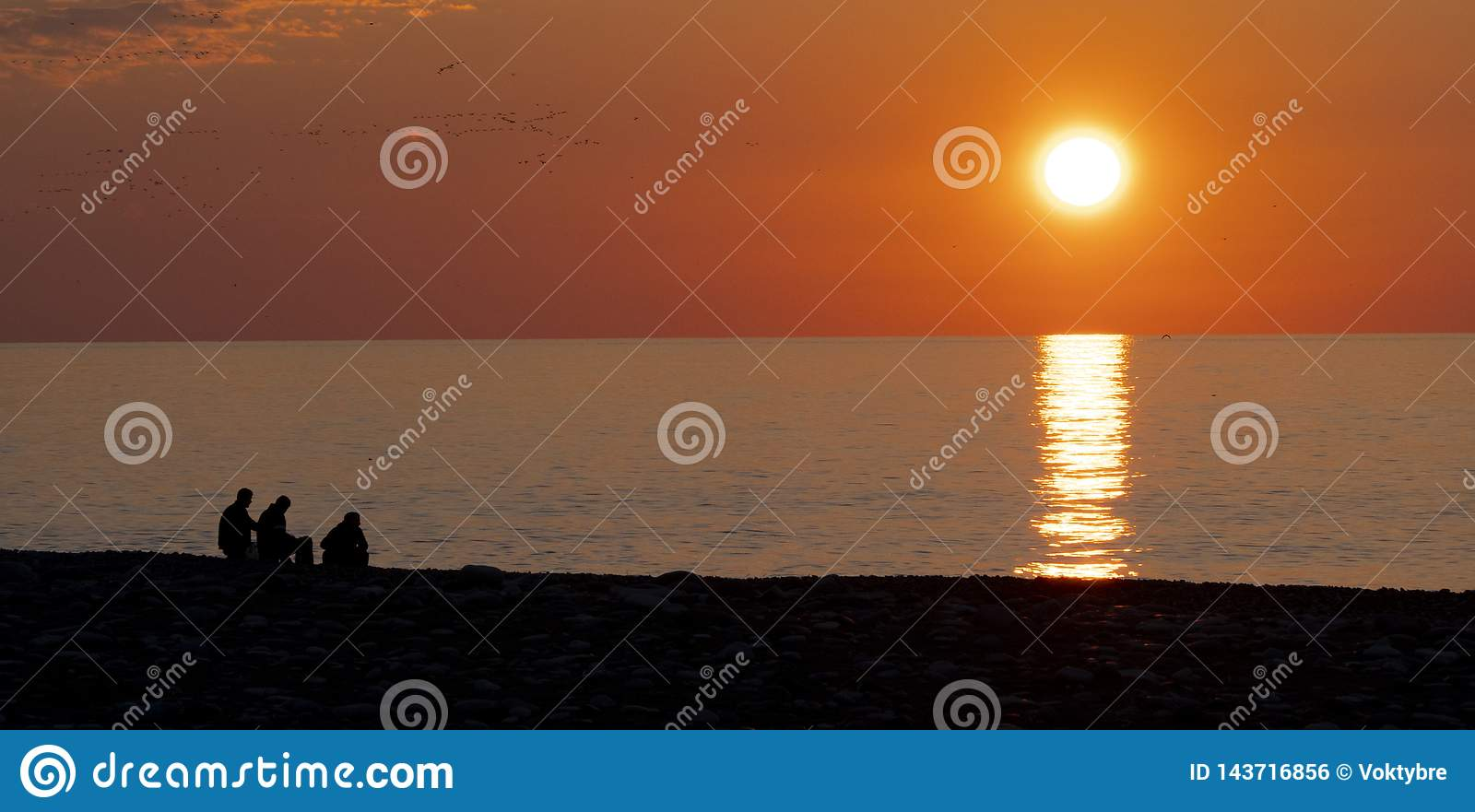 People on the background of the sunset and the sea on the waterfront