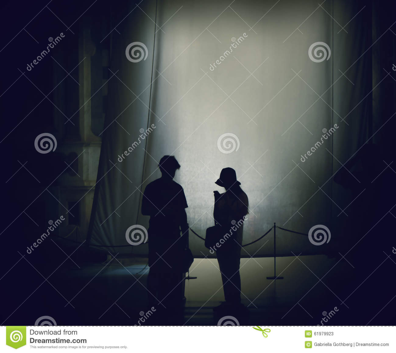 Silhouettes of people backlit in the great cathedral of Pisa.