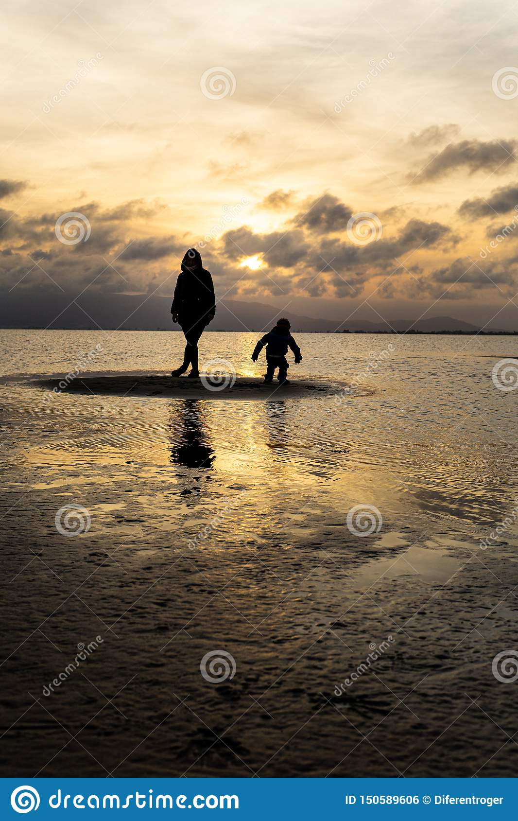 Silhouettes of unrecognizable people on the beach at sunset