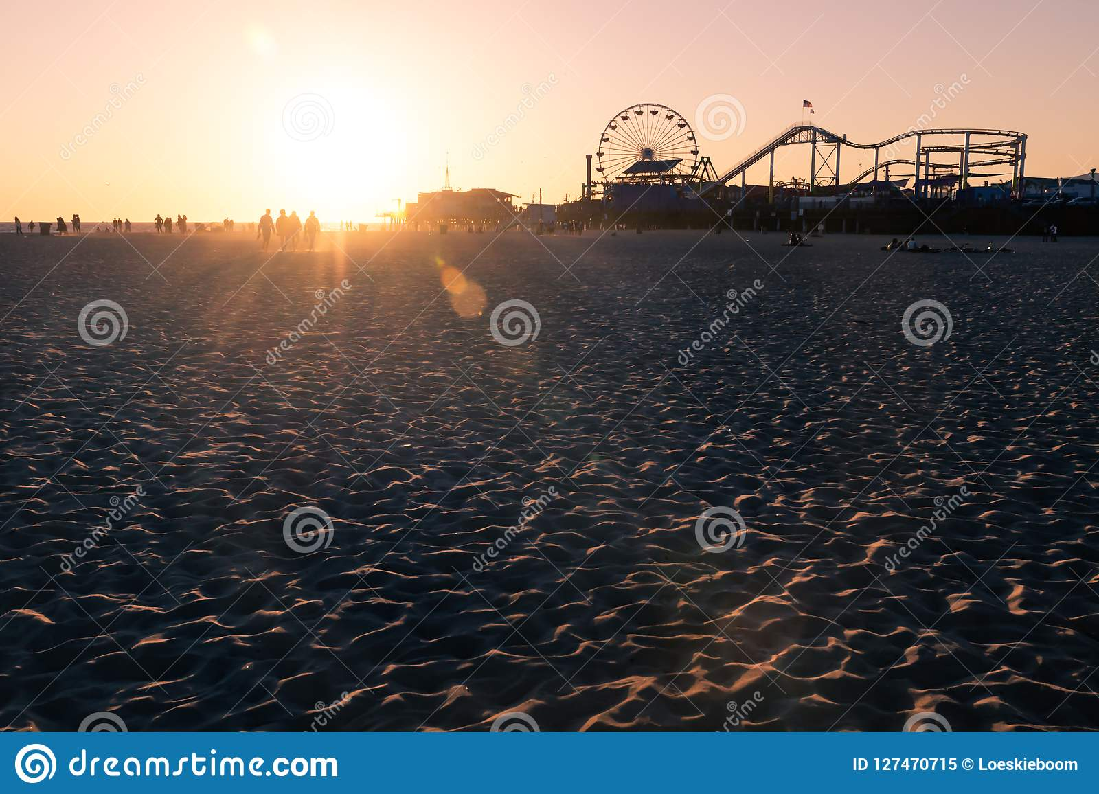Silhouettes of people walking along Santa Monica beach and amusement park at sunset, Los Angeles, California