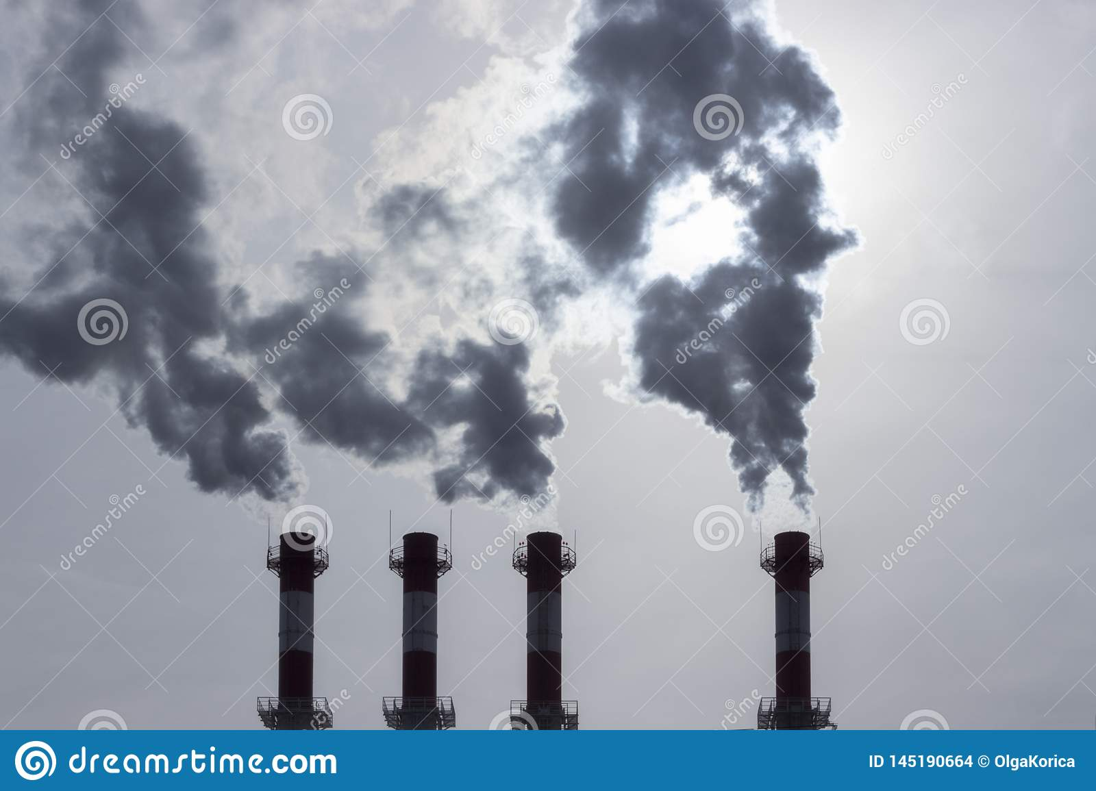 Silhouettes of pipes emitting dark steam into the atmosphere. air pollution by toxic fumes. Poisoned air atmosphere