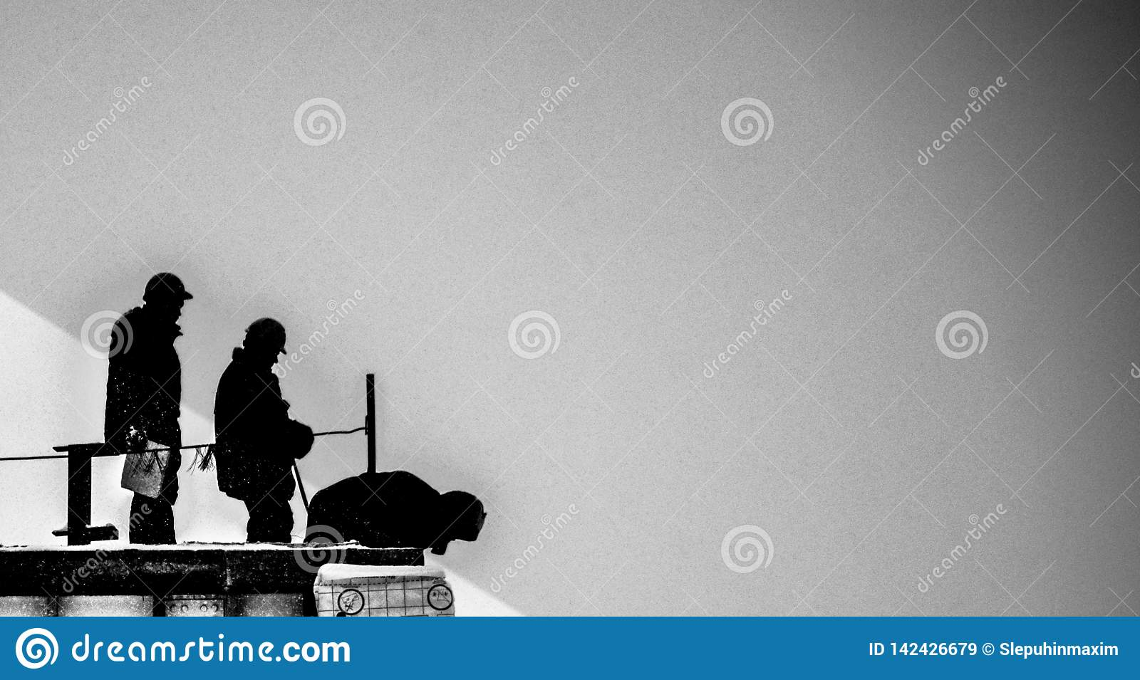 Silhouettes of three builders on a black-and-white background