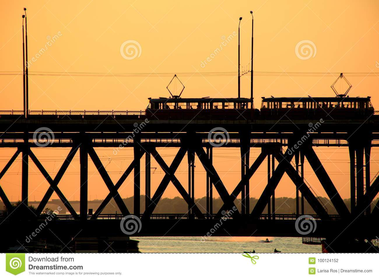 Silhouettes of a two-tiered bridge and 2 trams on a sunset background