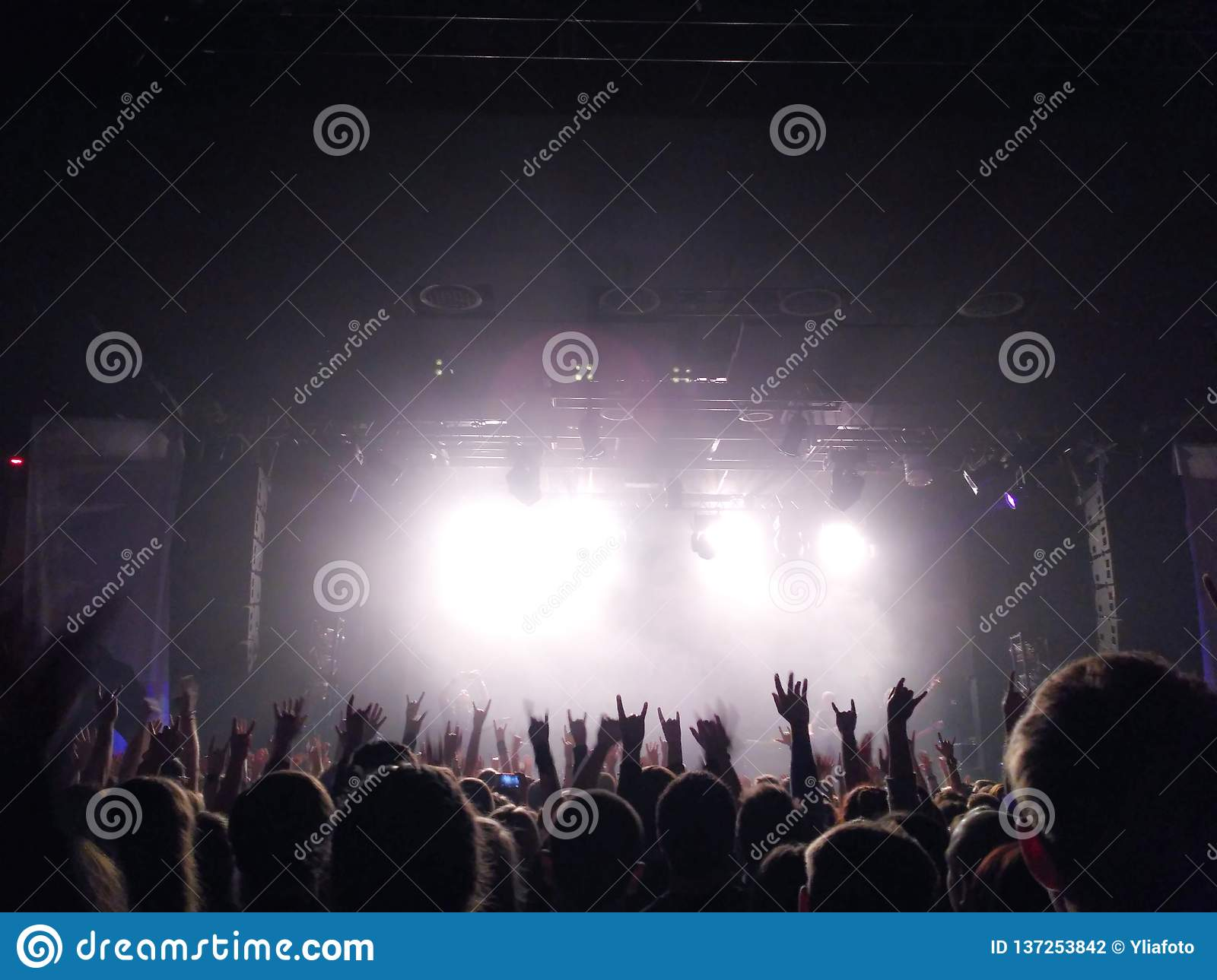 Silhouettes of young people with the raised hands up before a scene at a concert. Rock group. Bright light on the stage
