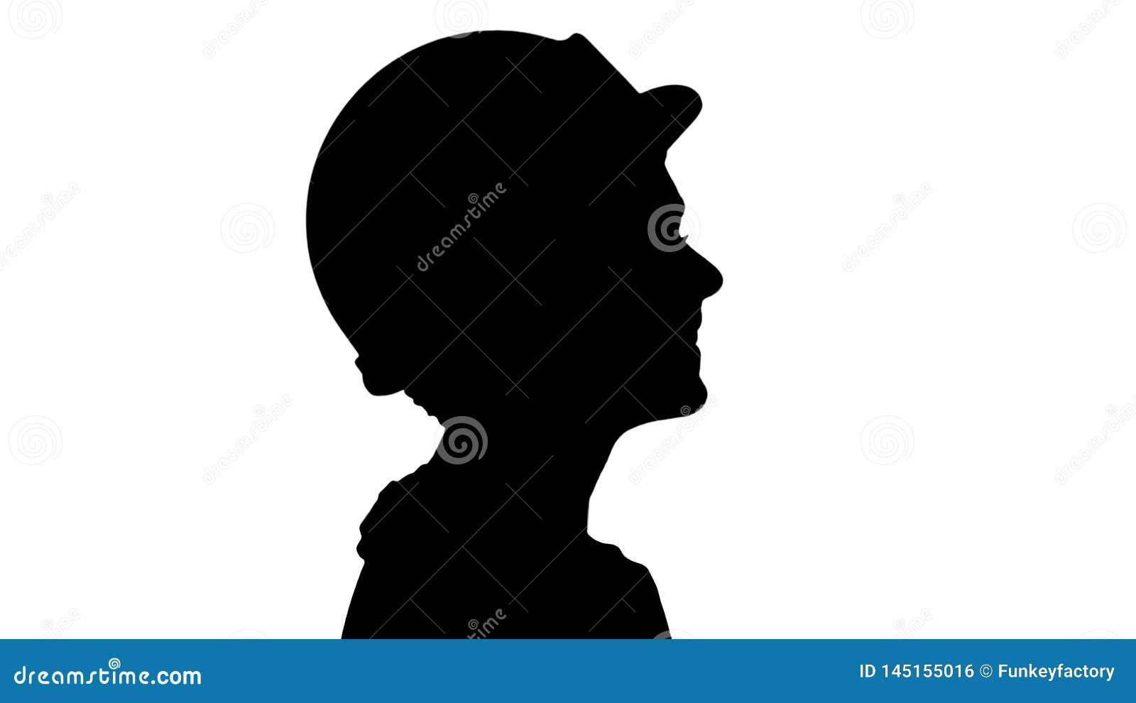Silhouettez l ing?nieur de jeune femme avec le casque de s?curit? jaune marchant et souriant