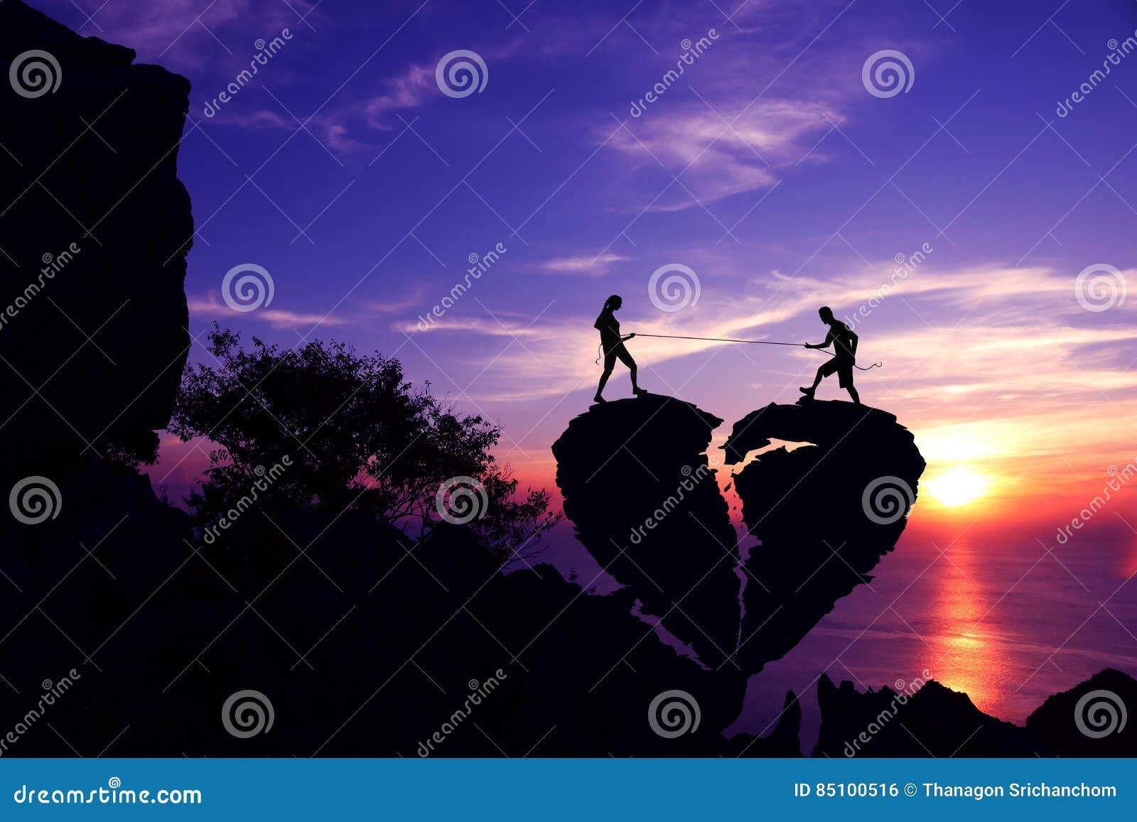 Silhouettez le concept de fond de Valentine, couples tirant la corde sur la pierre en forme de coeur cassée