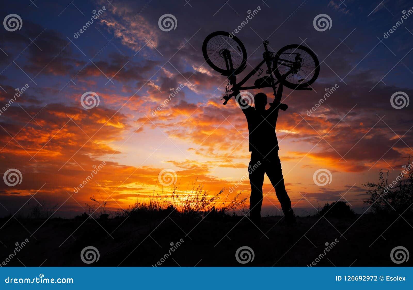 Silhouettieren Sie den Mannstand in anhebendem Fahrrad der Aktion