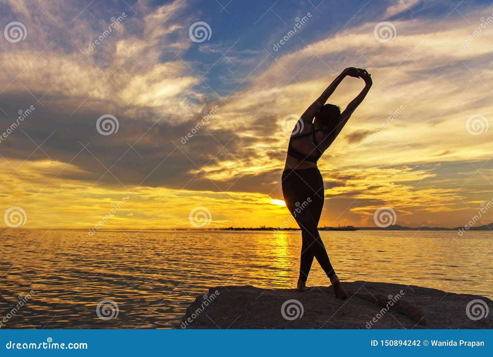 Silhouettieren Sie gesunde Frau, das Lebensstil, dentrainieren wesentlich und ?bendes Yoga auf dem Felsen im Strand bei Sonnenunt