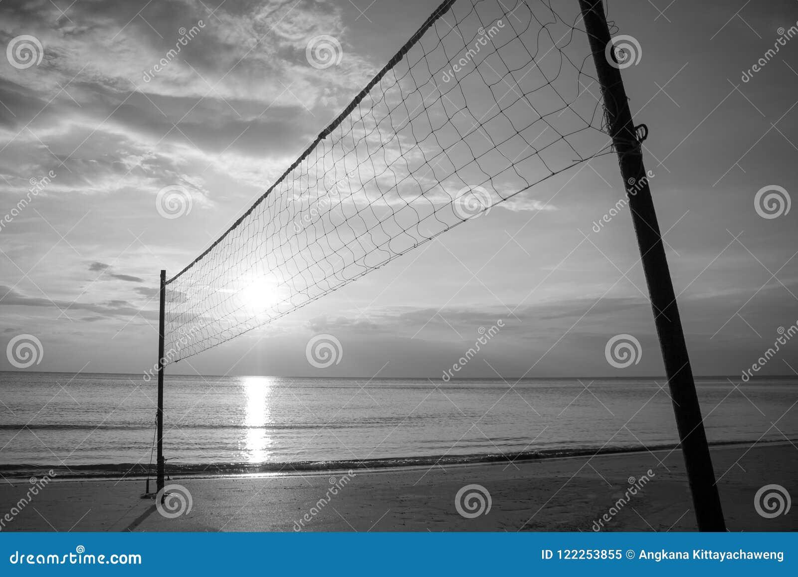Silhouettieren Sie Volleyballnetz auf Sandstrand mit schönem Sonnenuntergang in der Dämmerungszeit