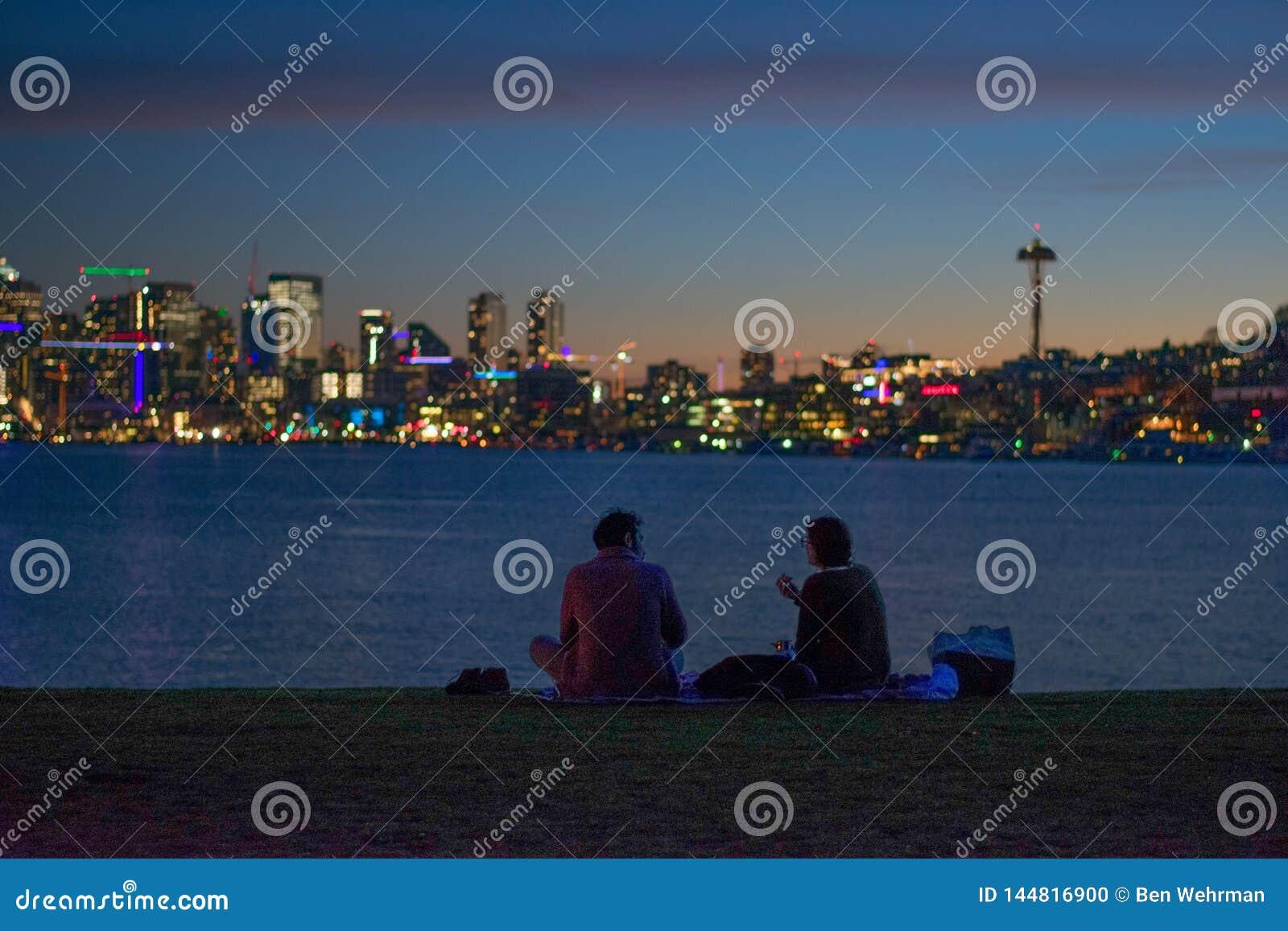 Silhouettiert Haben eines Picknicks in der Stadt
