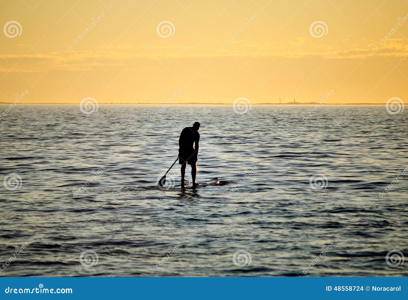 Silhoutte стоит вверх полощущ серфер