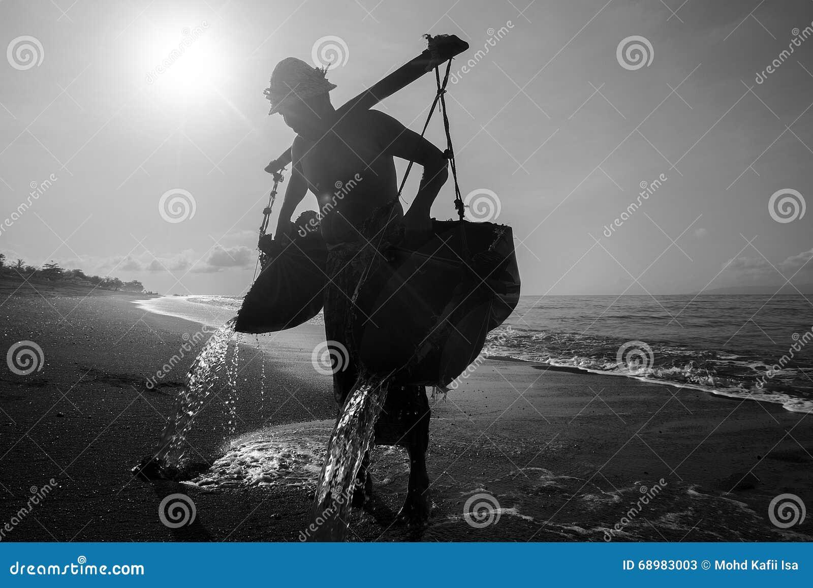 Silhoutte de la gente local que recoge la agua de mar