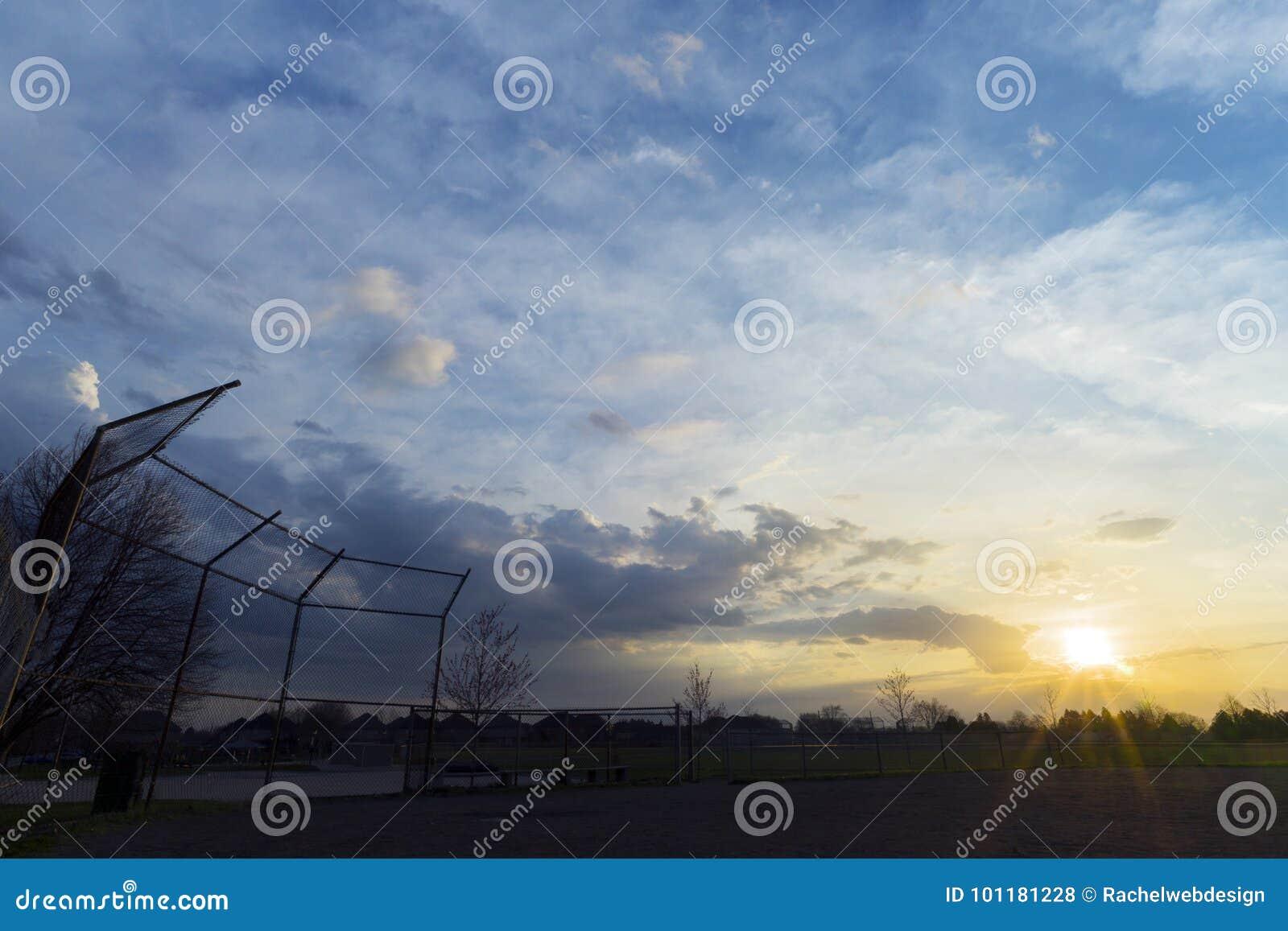 Silhueta da cerca do diamante de basebol no alvorecer, nascer do sol bonito