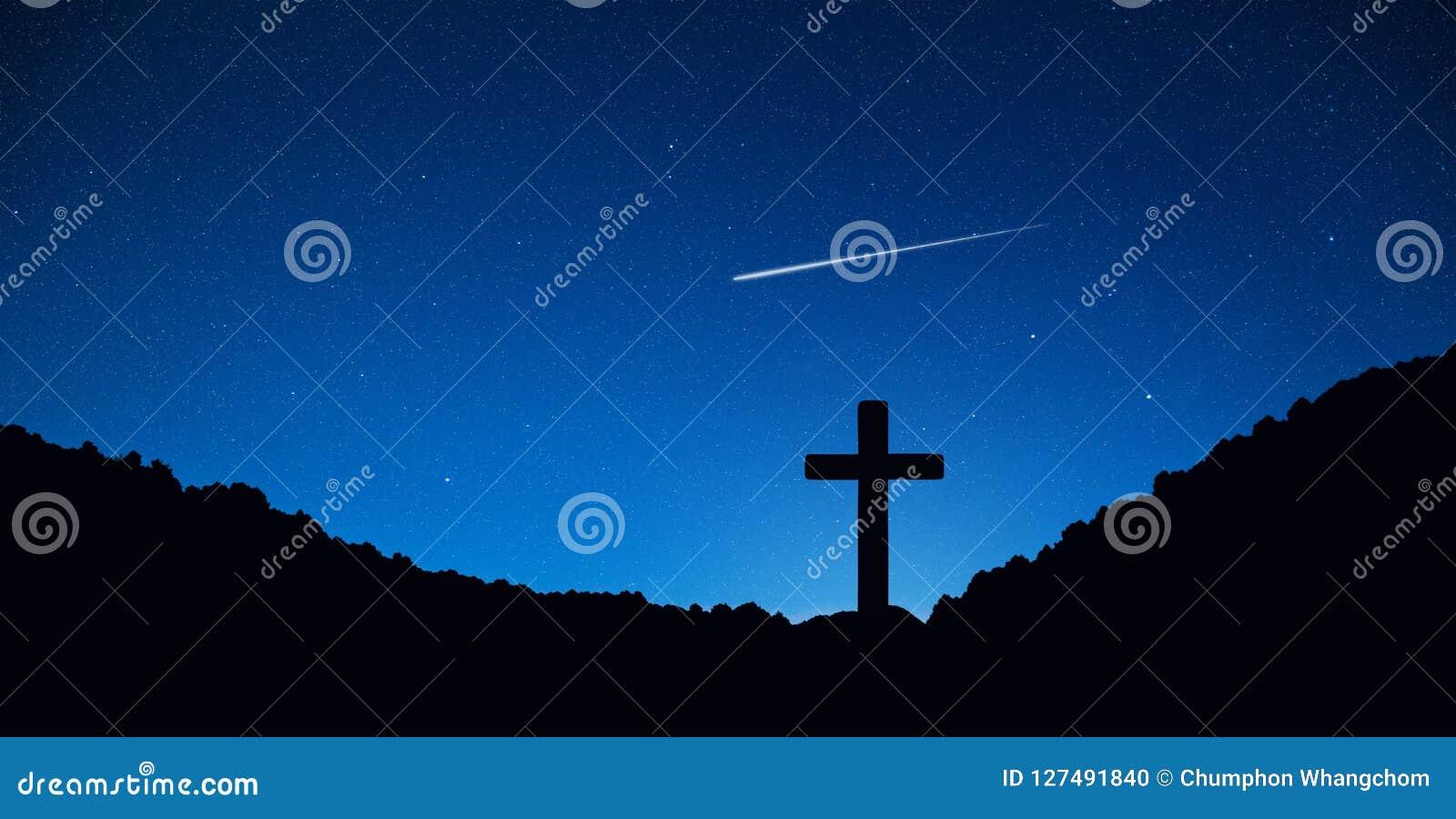 Silhueta da cruz do crucifixo na montanha na noite com fundo da estrela e do espaço