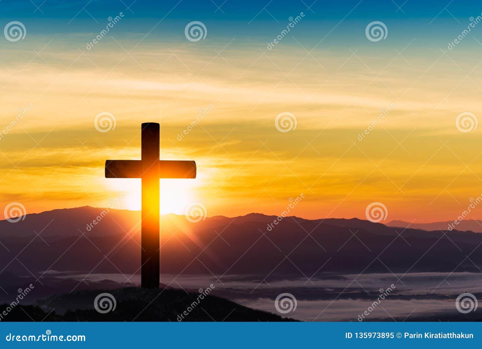 Silhueta da cruz no fundo do por do sol da montanha