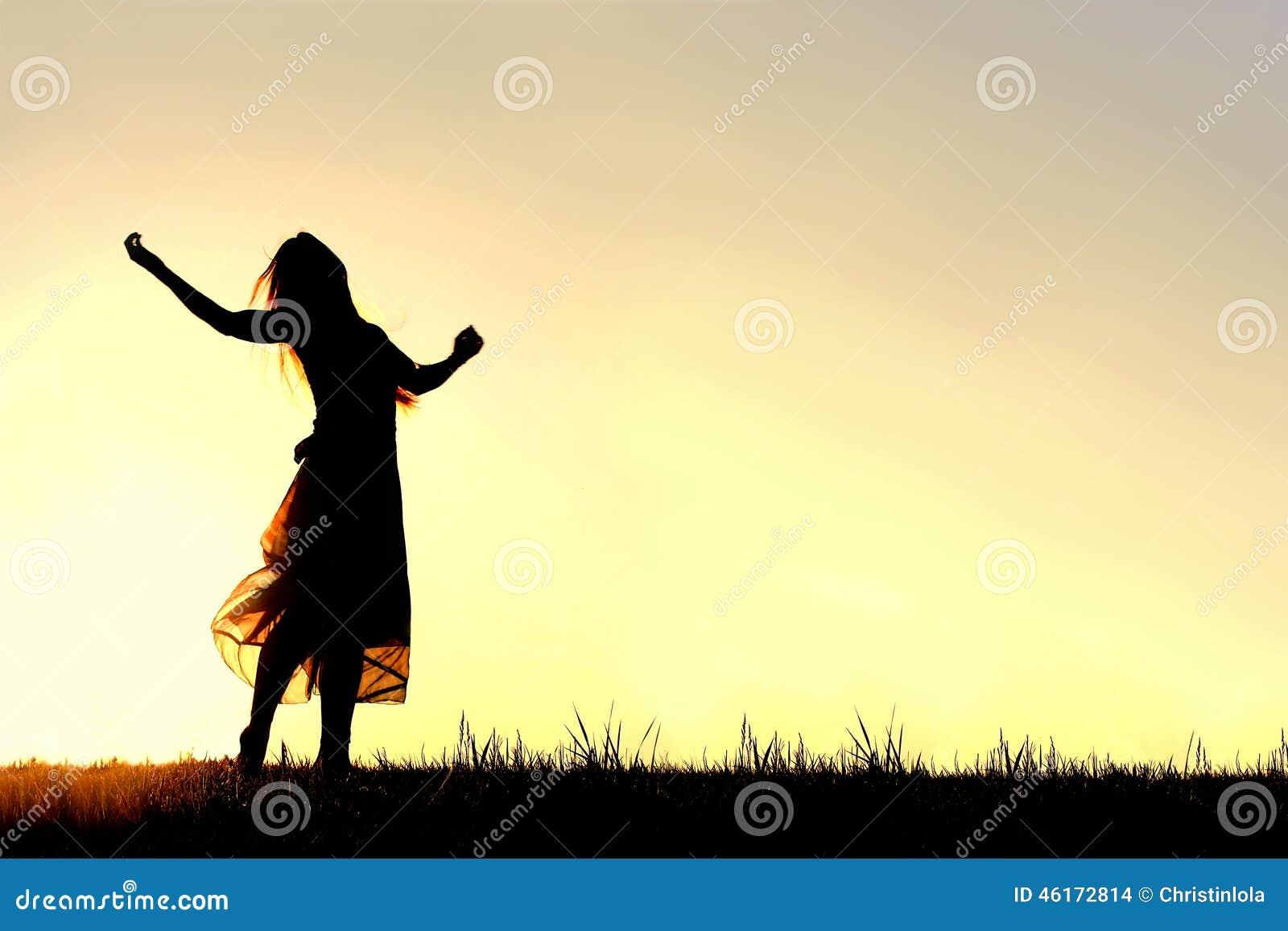 Silhueta da dança da mulher e do deus do elogio no por do sol