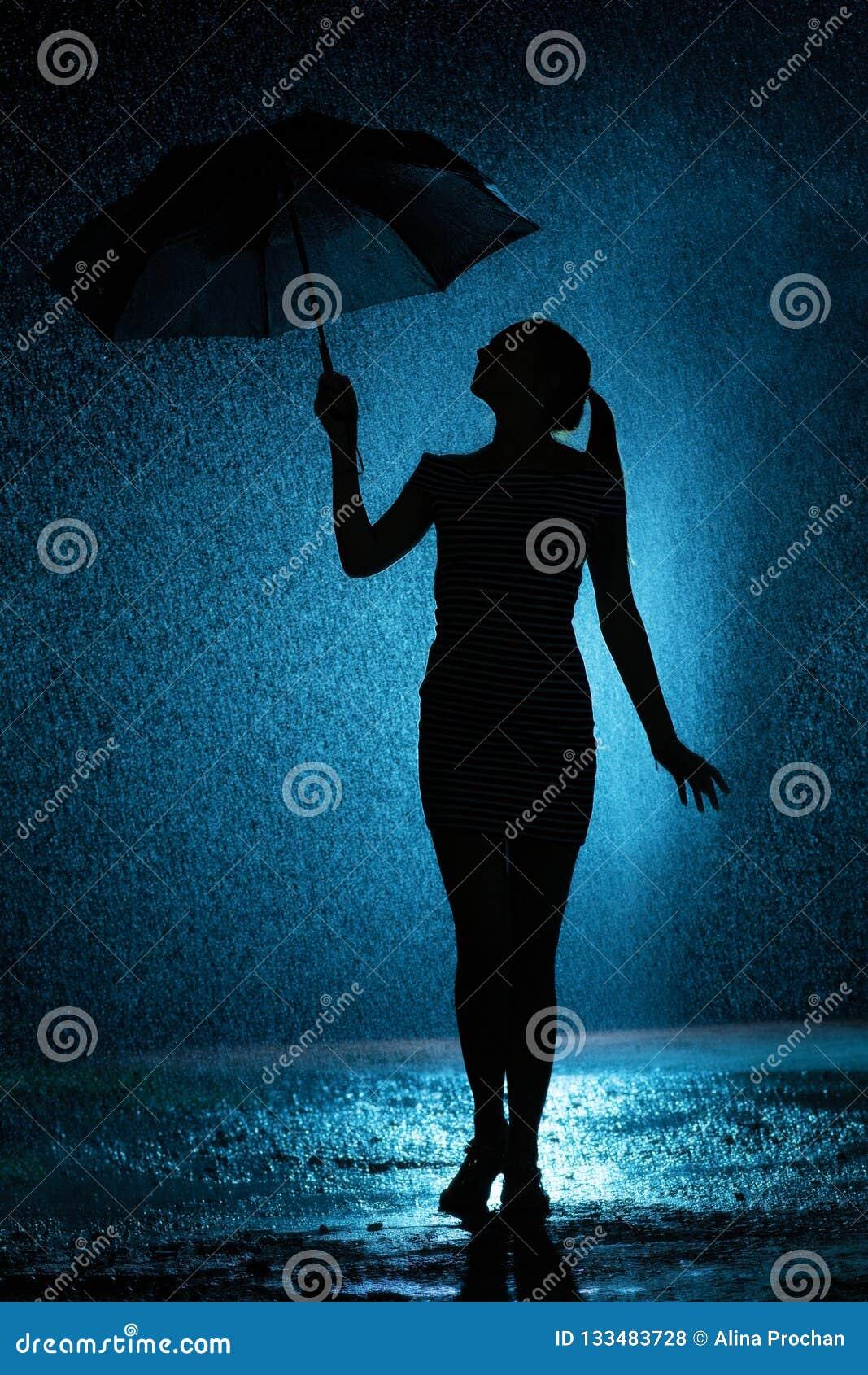 A silhueta da figura de uma moça com um guarda-chuva na chuva, uma jovem mulher está feliz às gotas da água, tempo do conceito