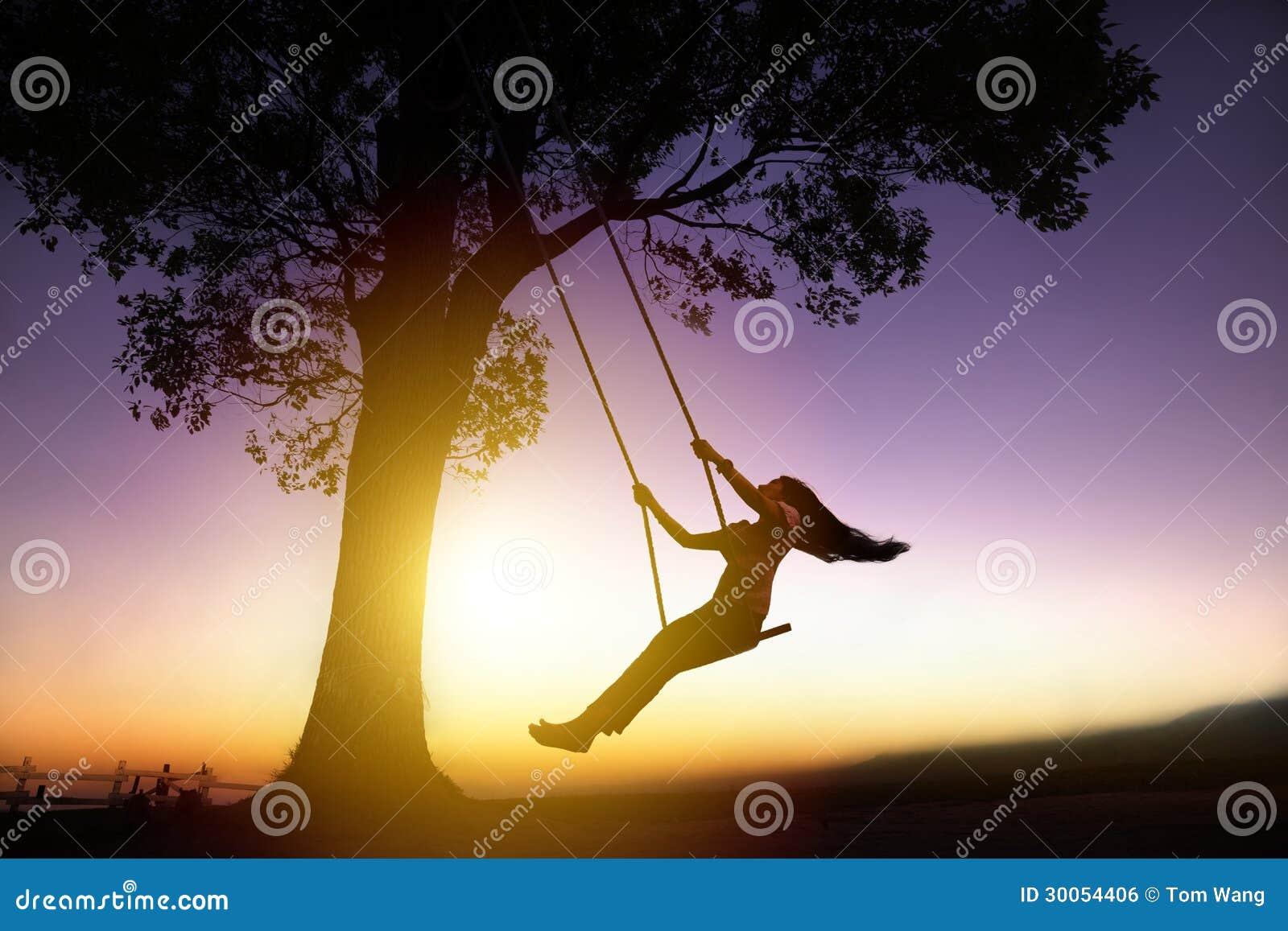Silhueta da jovem mulher feliz no balanço