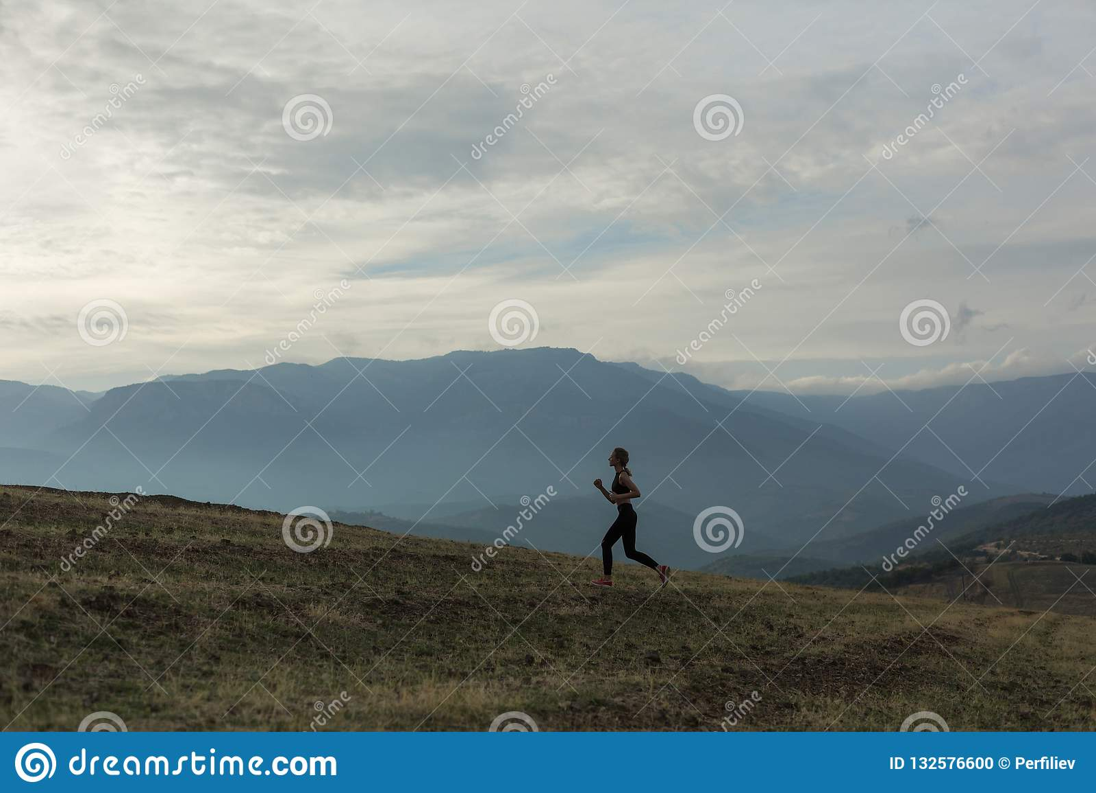 A silhueta da menina magro está movimentando-se em montanhas nevoentas
