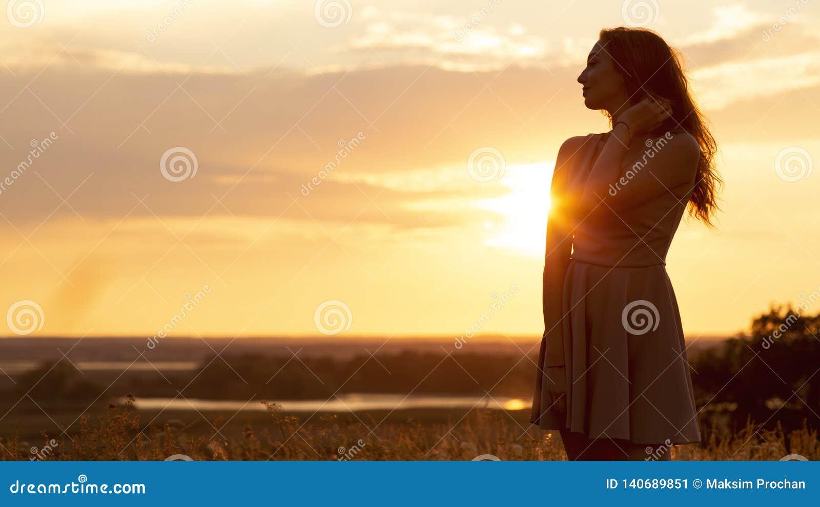 Silhueta da menina sonhadora em um campo no por do sol, uma jovem mulher em um embaçamento do sol que aprecia a natureza, estilo