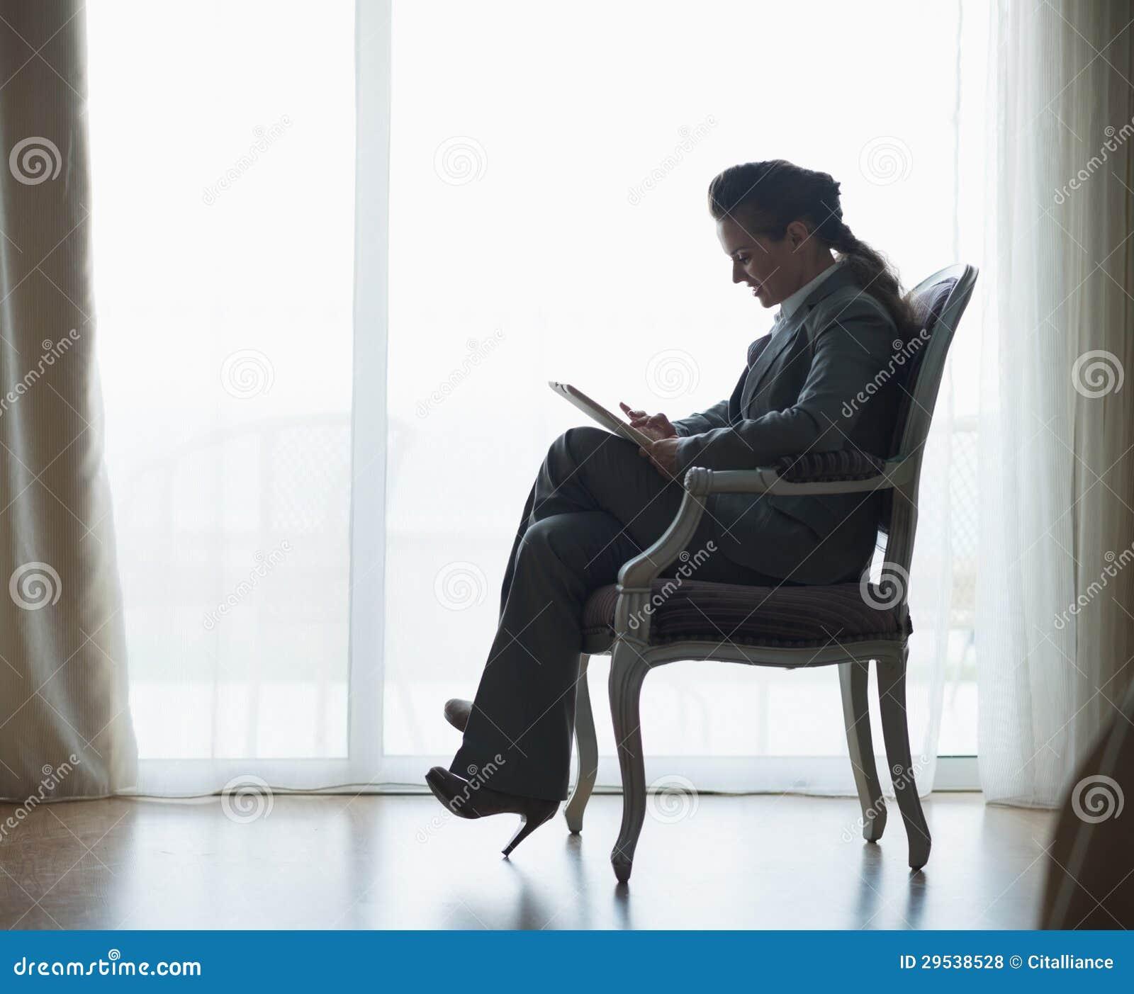 Silhueta da mulher de negócio que trabalha no PC da tabuleta