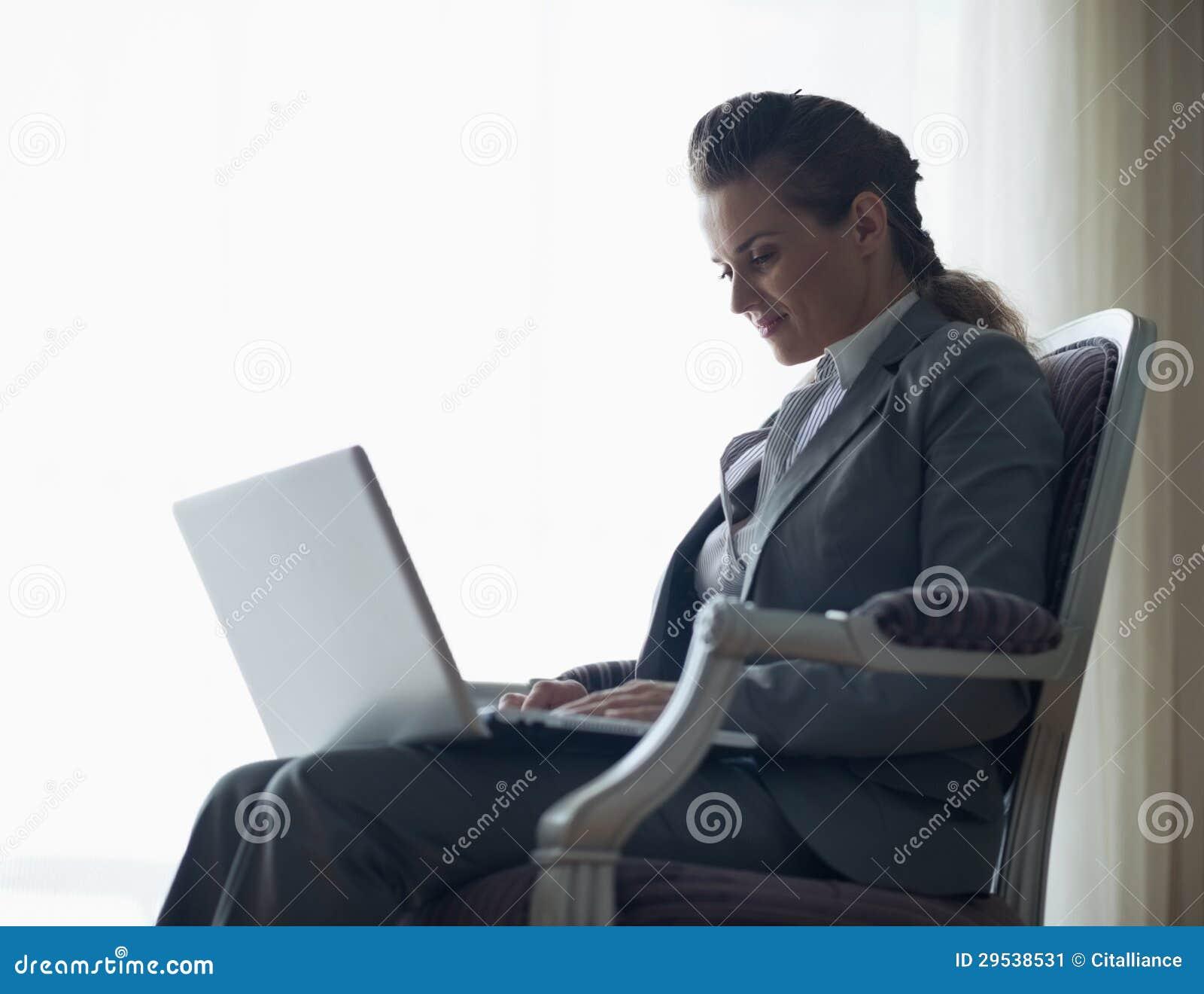 Silhueta da mulher de negócio que trabalha no portátil