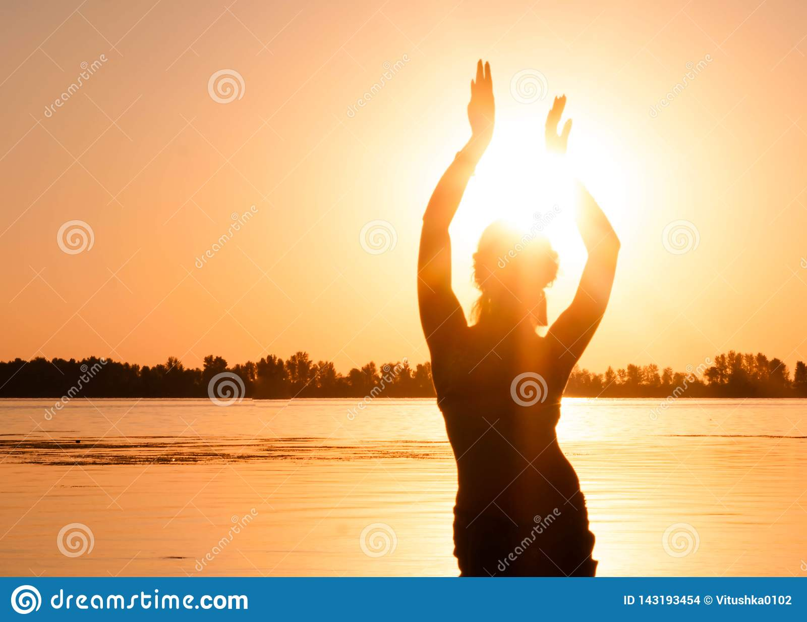 Silhueta da mulher magro que dança a dança do ventre tribal tradicional na praia no nascer do sol