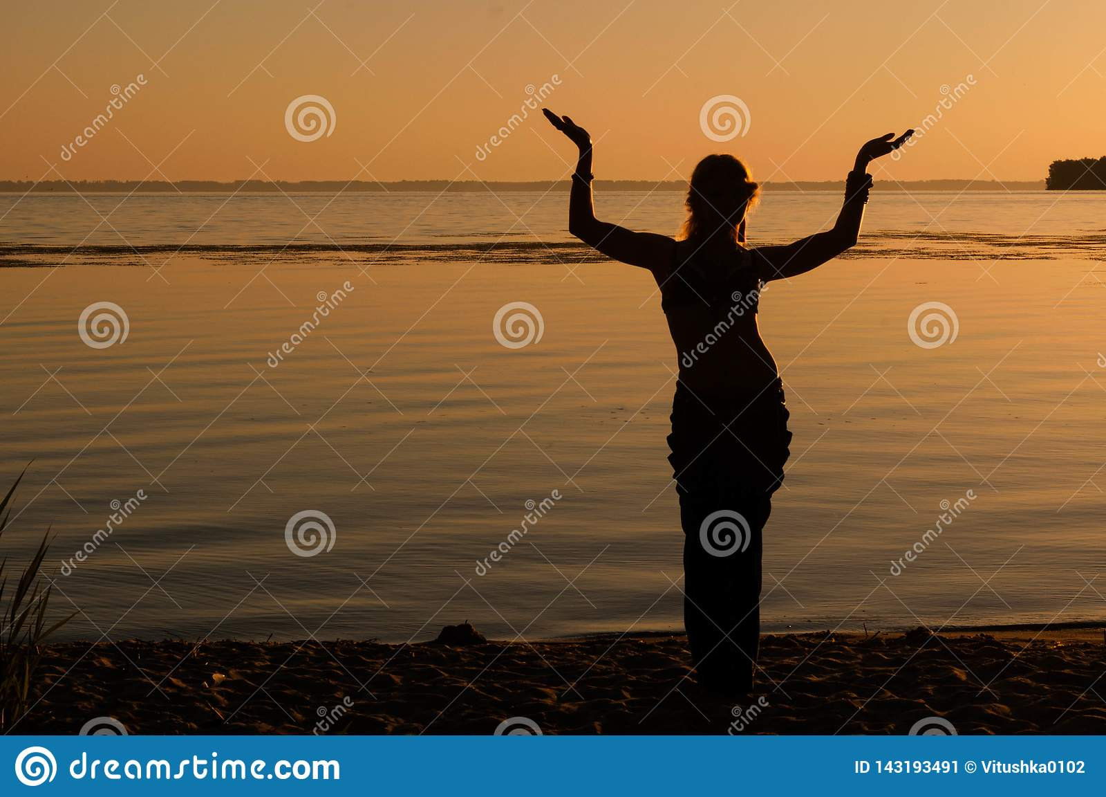 Silhueta da mulher que dança oriental trible da tradição perto da costa grande do rio
