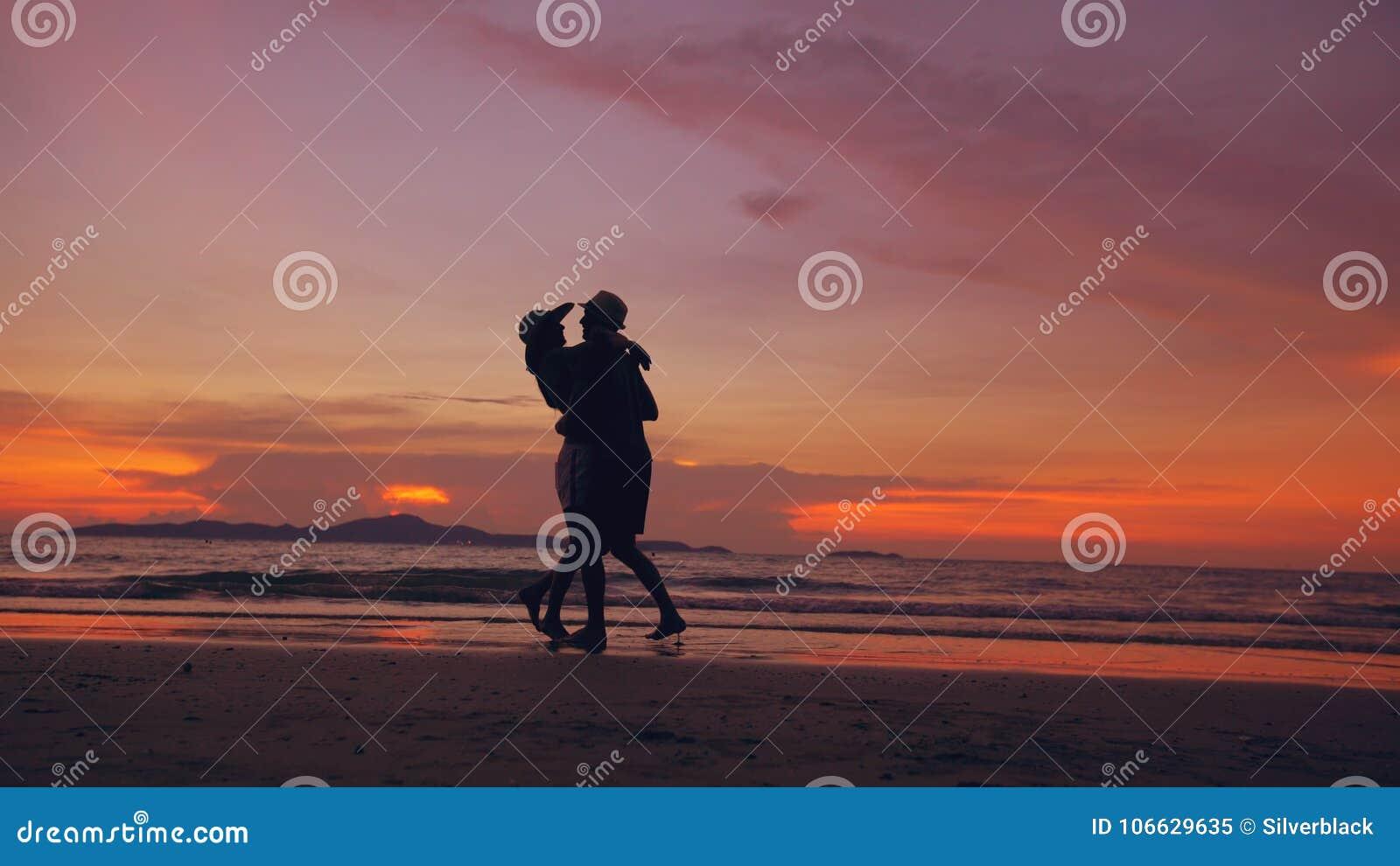 A silhueta de pares loving felizes encontra-se e joga-se na praia no por do sol na costa do oceano