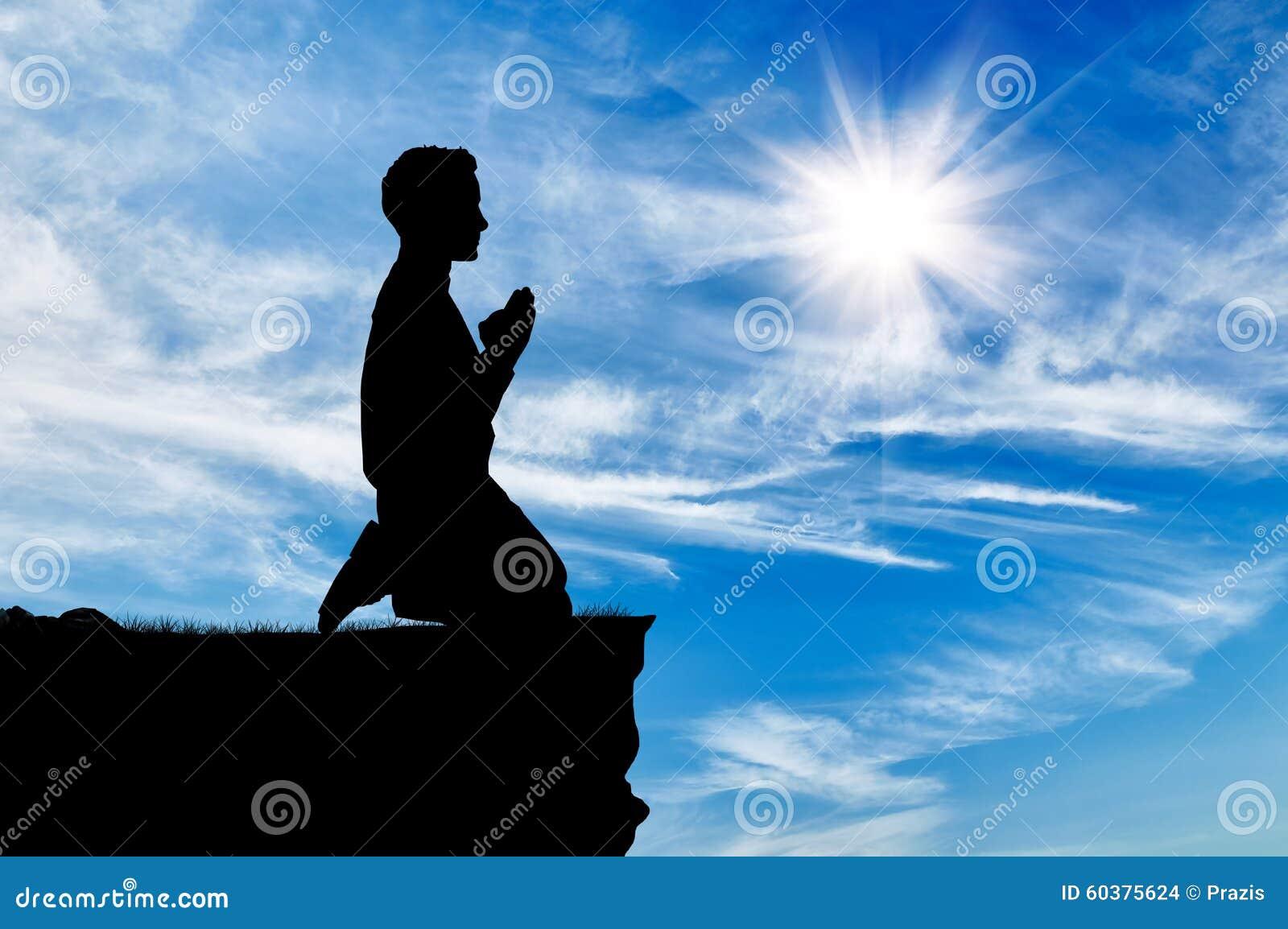 Silhueta de rezar do homem