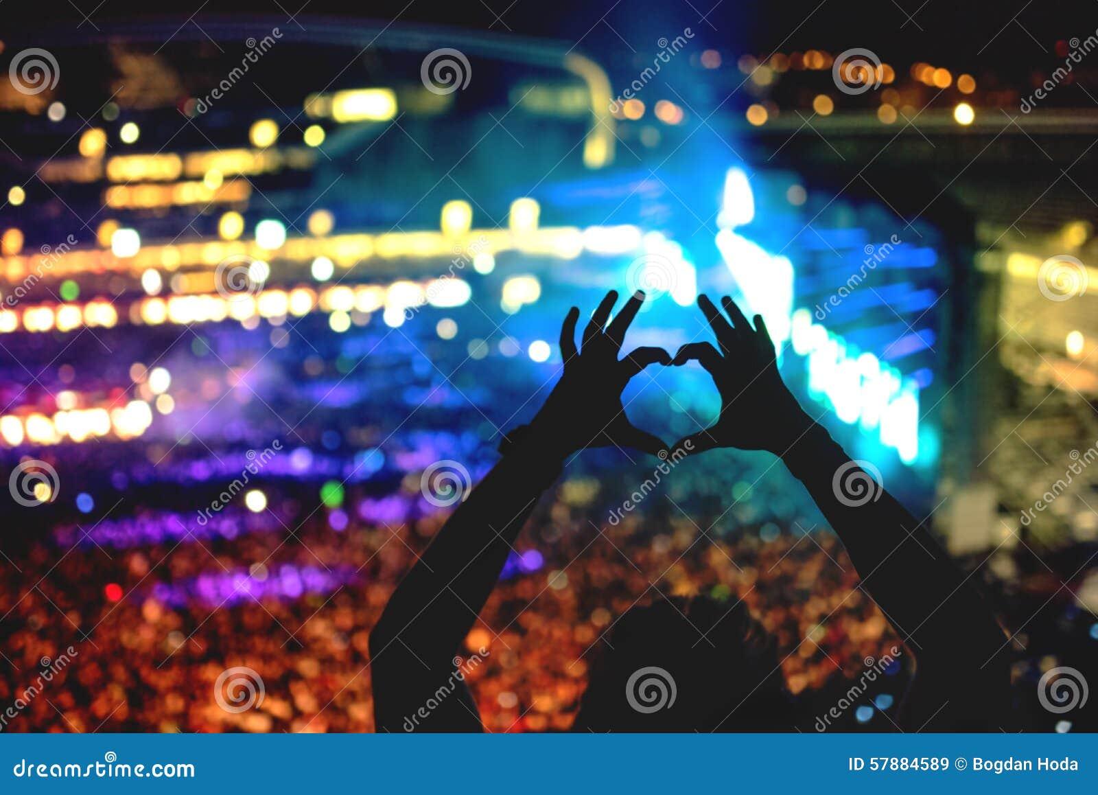 Silhueta de um homem que faz o coração dos gestos de mão, o olhar do vintage na foto e o fundo da multidão