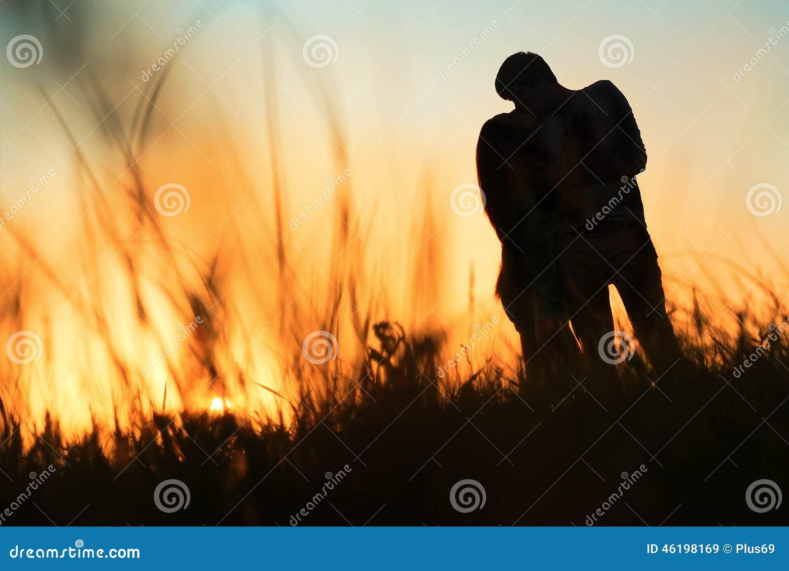 Silhueta de um par novo que beija no por do sol