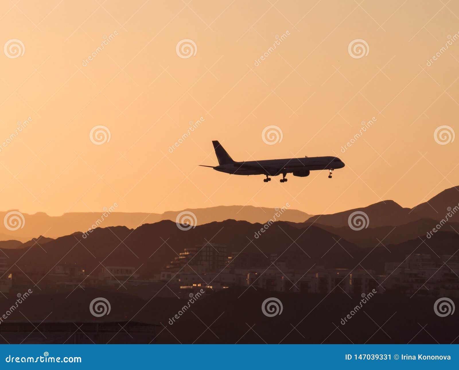 Silhueta de um ponto baixo de voo plano sobre a cidade e as montanhas no por do sol