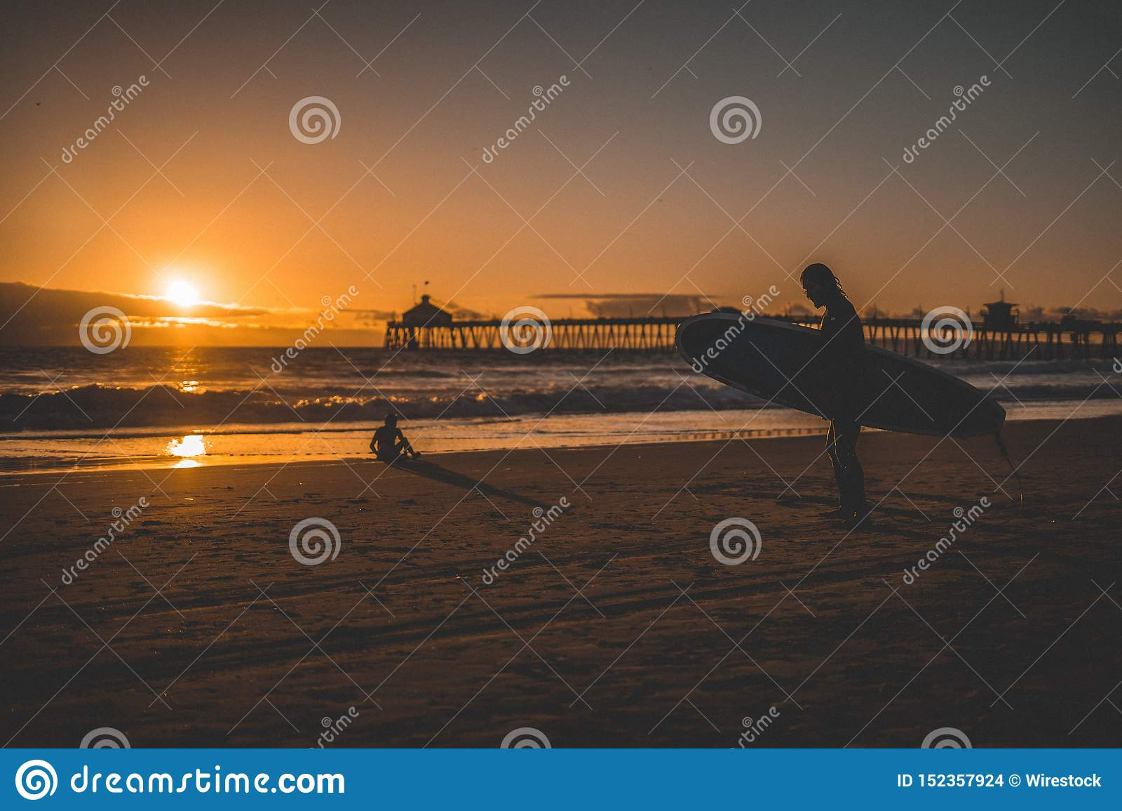 Silhueta de um surfista em um Sandy Beach com o por do sol no fundo