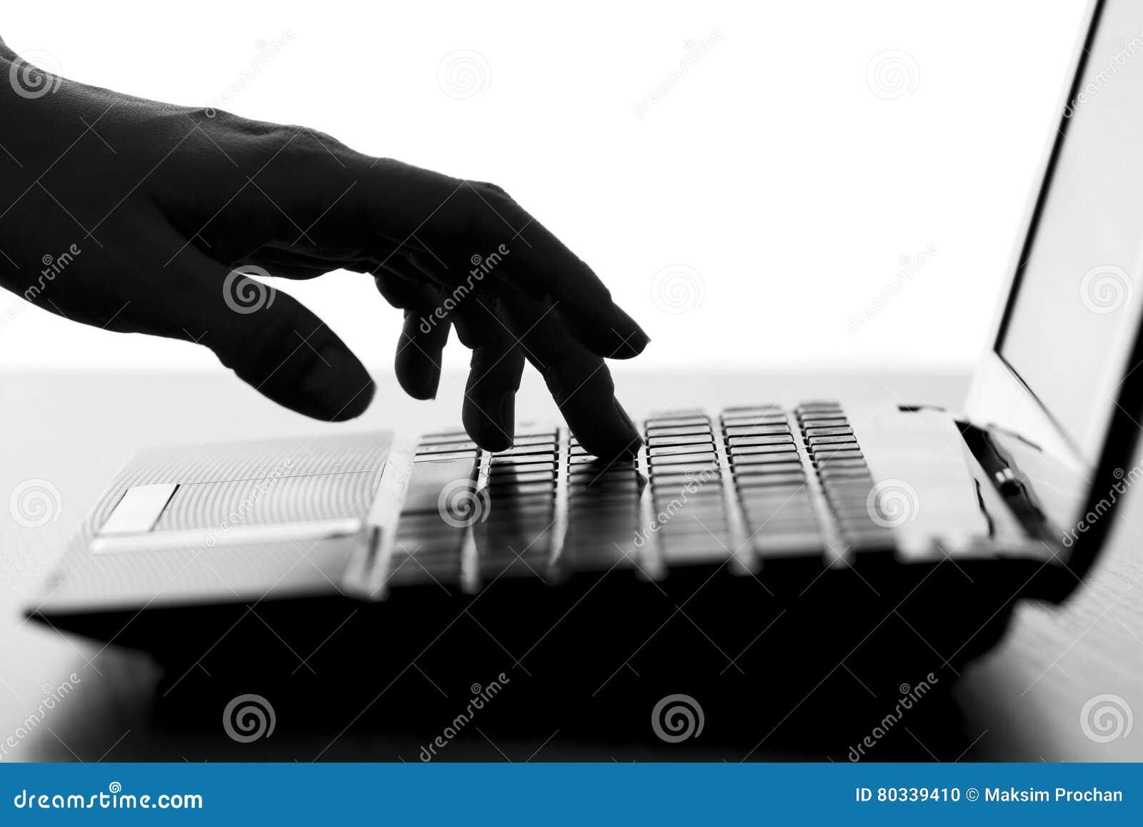 A silhueta de uma fêmea entrega a datilografia no teclado do netbook