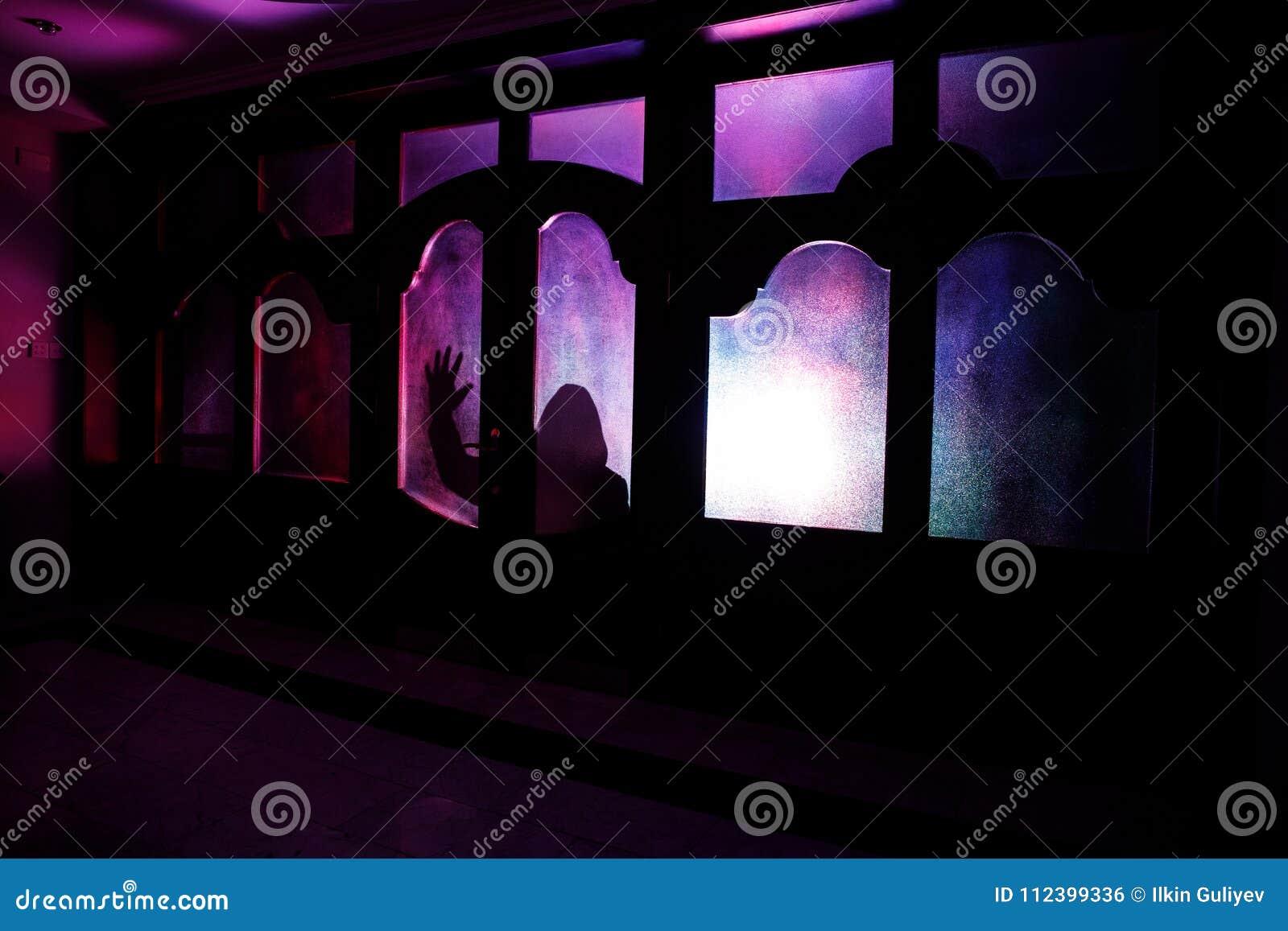 Silhueta de uma figura desconhecida da sombra em uma porta através de uma porta de vidro fechado A silhueta de um ser humano na f