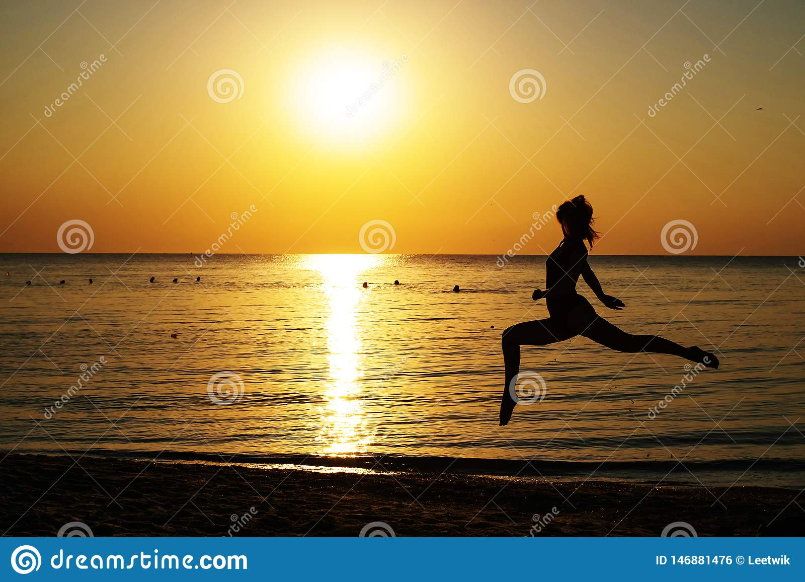 Silhueta de uma menina em um mai? que corre ao longo da praia no fundo do alvorecer